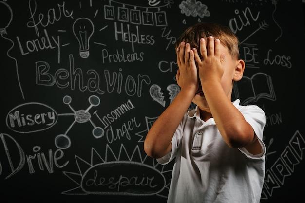 Criança com depressão em um fundo preto com as mãos fechadas