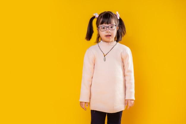 Criança com desordem genética. menina curiosa com síndrome de down posando contra uma parede laranja usando um suéter quente e macio