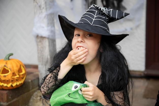 Criança com fantasia de bruxa fofa, mas assustadora