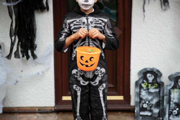 Criança com fantasia de esqueleto fofa, mas assustadora