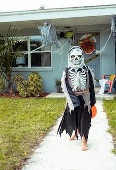 Criança com fantasia de halloween menino com fantasia de esqueleto com balde de doces doces ou guloseimas do lado de fora