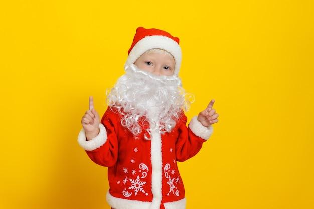 Criança com fantasia de papai noel de natal e barba falsa branca mostrando o dedo indicador apontando para cima