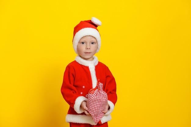 Criança com fantasia de papai noel de natal e uma barba branca segurando a ruiva em uma sacola branca com presentes