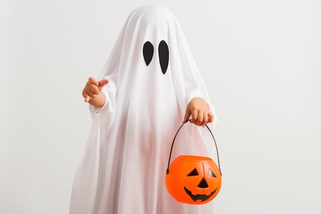 Criança com fantasia vestida de branco fantasma de halloween assustador ele segurando o fantasma de abóbora laranja na mão