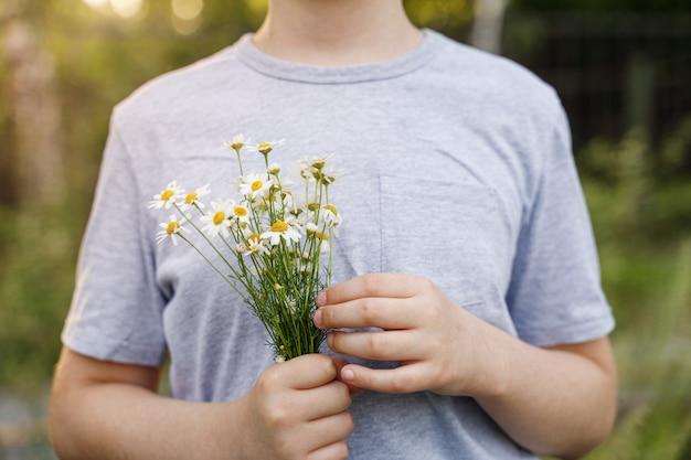 Criança com flor da margarida no prado.