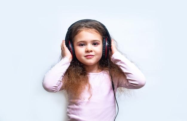 Criança com fones de ouvido isolados no branco