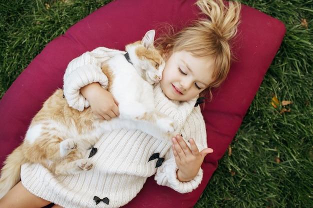 Criança com gato deitado sobre um cobertor no jardim, cuidando dos animais. criança com gatinho posa no quintal. infância feliz