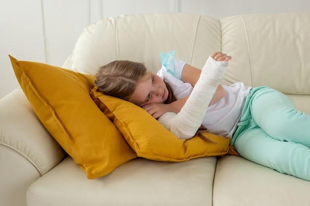 Criança com gesso em um pulso ou braço quebrado deitada em um sofá de recuperação e conceito de criança