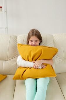 Criança com gesso em um pulso ou braço quebrado sentada em um sofá