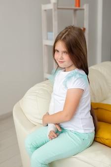 Criança com gesso em um pulso ou braço quebrado, sorrindo e se divertindo em um sofá. atitude positiva, recuperação e conceito de criança.