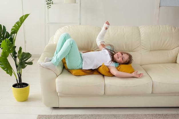 Criança com gesso em um pulso ou braço quebrado, sorrindo e se divertindo em um sofá. atitude positiva