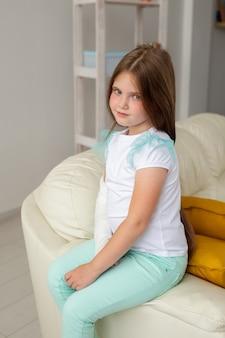 Criança com gesso em um pulso ou braço quebrado sorrindo e se divertindo em um sofá