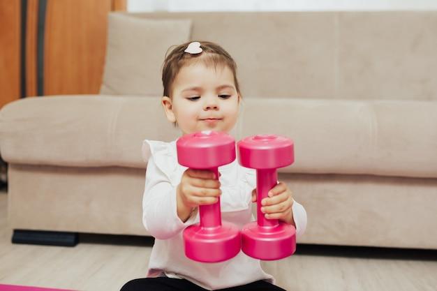 Criança com halteres em casa