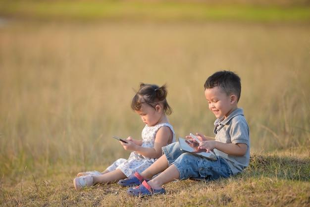 Criança com irmãos tablet.happy deitado ao ar livre e brincando com o tablet pc juntos.