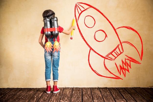 Criança com jet pack desenhar esboço na parede. criança brincando em casa. conceito de sucesso, líder e vencedor