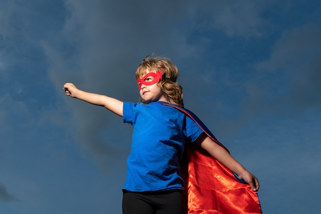Criança com manto de super homem. menino brincando de super-herói. conceito de vencedor de sucesso e crianças.