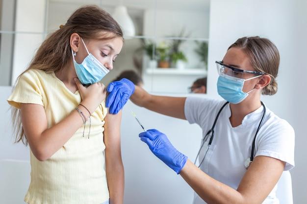 Criança com máscara facial sendo vacinada, coronavírus, covid-19 e conceito de vacinação.