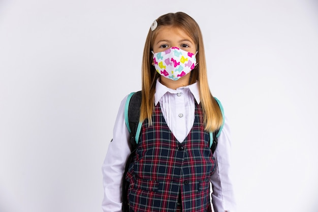 Criança com máscara facial voltando para a escola após quarentena e bloqueio covid-19. isolado na parede cinza.