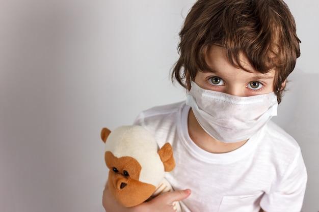 Criança com máscara médica com macaco de brinquedo
