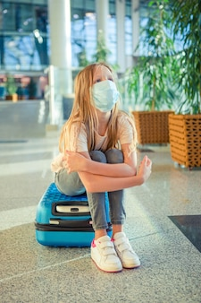 Criança com máscara médica no aeroporto esperando o embarque