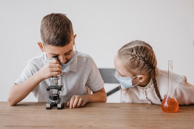 Criança com máscara médica olhando através de um microscópio