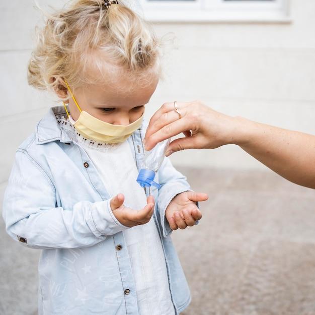 Criança com máscara médica recebendo desinfetante para as mãos