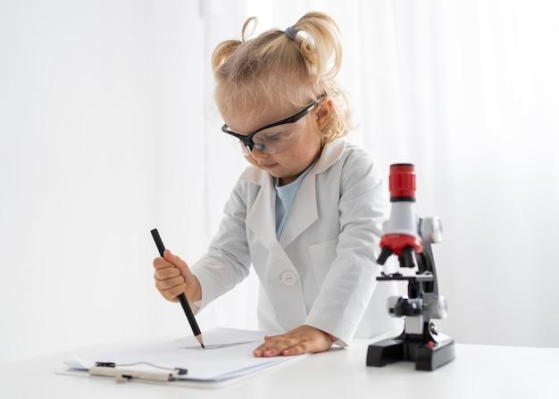 Criança com microscópio e óculos de segurança