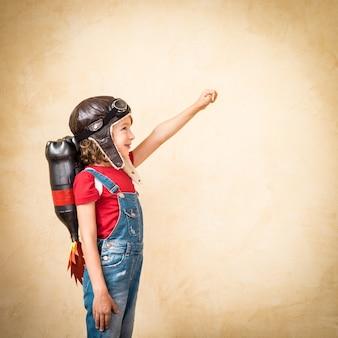 Criança com mochila a jato. criança brincando em casa. conceito de sucesso, líder e vencedor