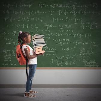 Criança com mochila e uma pilha de livros de estudo com quadro-negro