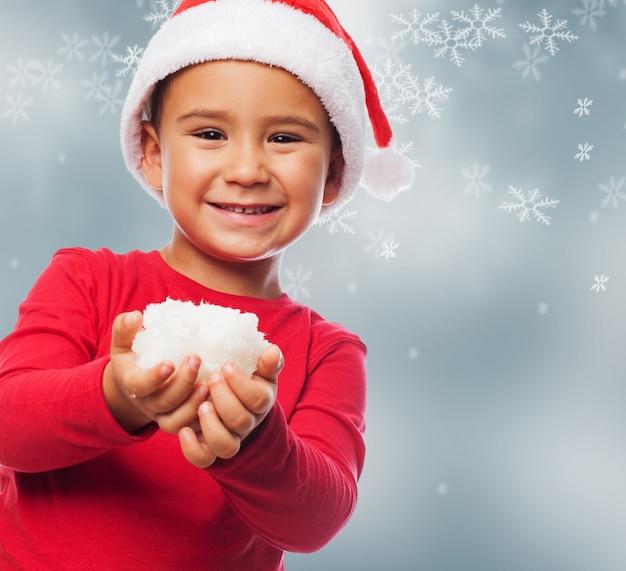 Criança com neve em suas mãos e fundo da neve
