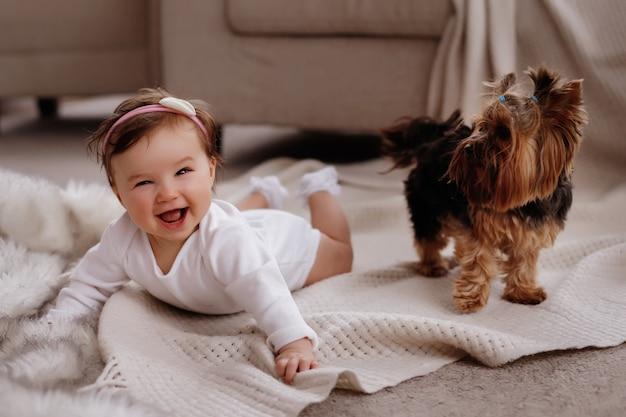 Criança com o cachorro deitado no tapete em casa
