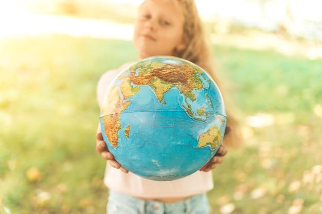 Criança com o retrato do globo terrestre de uma loira européia do ensino fundamental com um educ ...