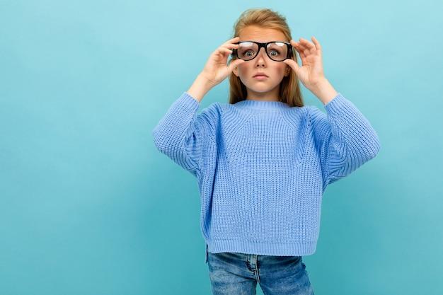 Criança com óculos e baixa visão sobre um fundo azul