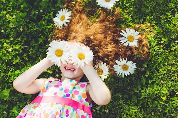 Criança com os olhos da margarida que encontram-se na grama verde.