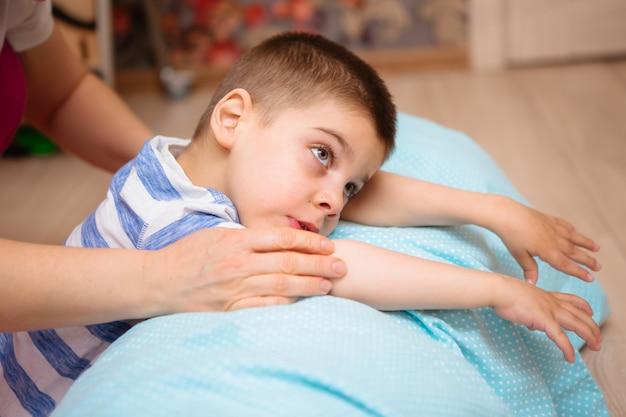 Criança com paralisia cerebral faz terapia musculoesquelética fazendo exercícios