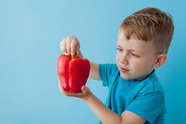 Criança com pimenta nas mãos sobre fundo azul. conceito vegano e saudável