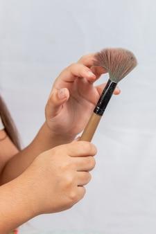 Criança com pincéis de maquiagem com fundo branco no rio de janeiro brasil