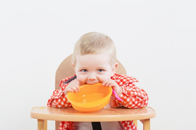 Criança com prato e colher na parede do fundo branco