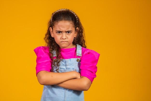 Criança com raiva, cruzando os braços. sobre fundo amarelo.