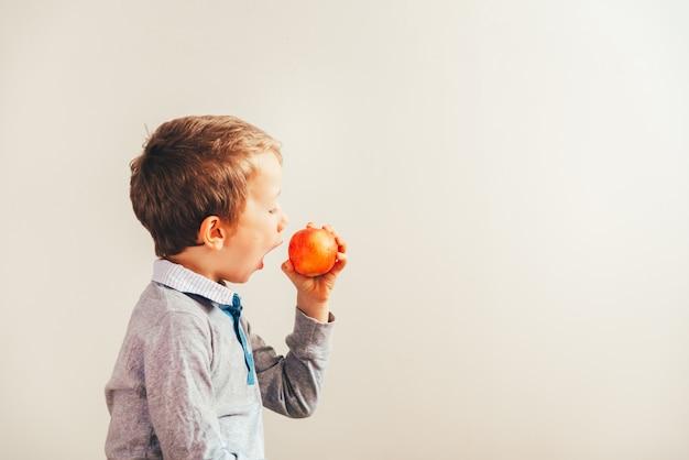 Criança com raiva e triste forçada a comer uma maçã.