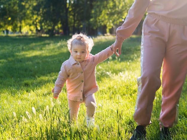 Criança com roupas cor de rosa em pé na grama