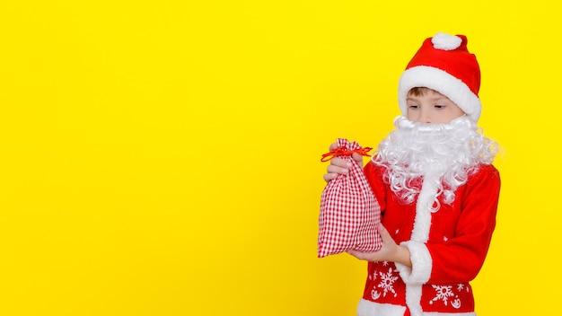 Criança com roupas de papai noel e barba artificial segurando uma pequena sacola com presentes de ano novo nas mãos