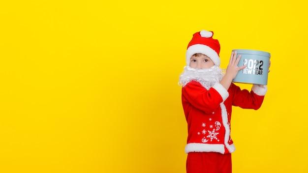 Criança com roupas de papai noel e com barba segurando uma caixa de presente no alto das mãos com as palavras ano novo