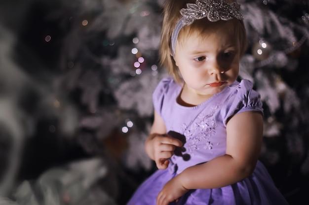 Criança com roupas elegantes na frente da árvore de natal. véspera de ano novo. esperando pelo novo ano.