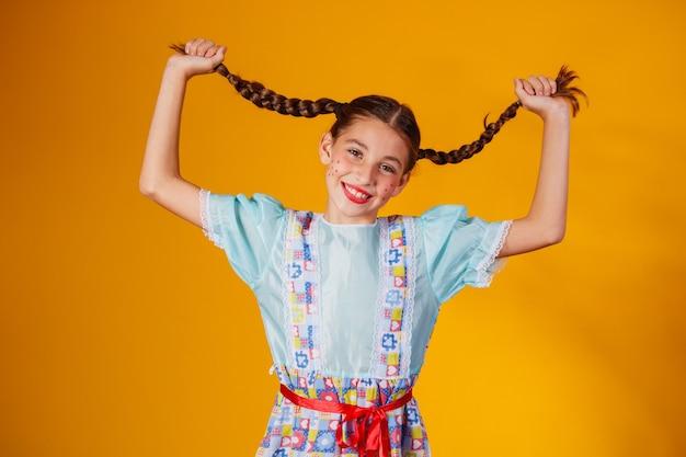 """Criança com roupas típicas da famosa festa brasileira chamada """"festa junina"""" em comemoração a são joão. garota linda."""