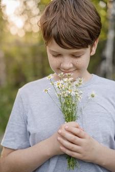 Criança com sardas no rosto cheirando uma flor margarida no prado.