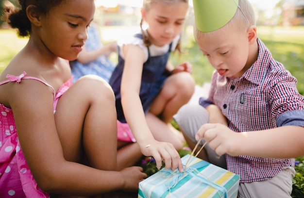 Criança com síndrome de down com amigos na festa de aniversário ao ar livre no jardim, abrindo presentes.