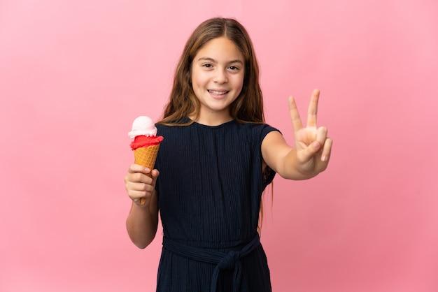 Criança com sorvete de corneta sobre rosa isolada sorrindo e mostrando sinal de vitória