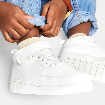 Criança com tênis jeans branco