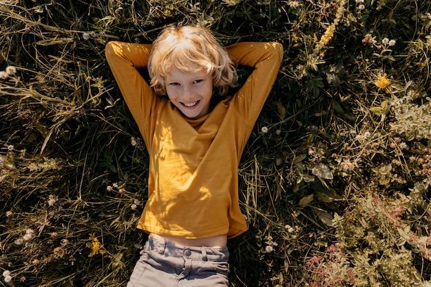 Criança com tiro médio deitado na grama